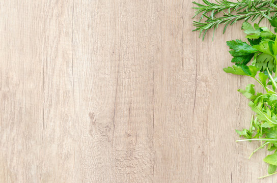 Wooden cutting or chopping board parsley basil herbs flat lay background with copy space