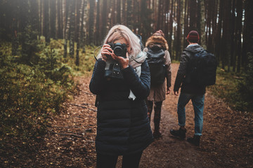 Young blond woman is making a photo with her camera while walking in forest with her friends.