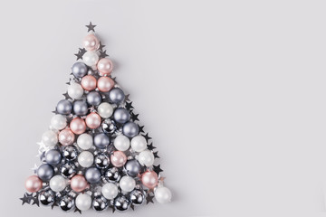 Christmas tree made of stars, confetti, silver pastel balls on grey background. Xmas composition. Flat lay, top view, copy space. Holiday Greeting card.