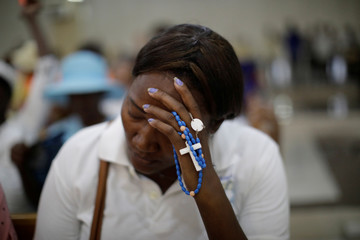 A woman holds a rosary as she sits at Christ Roi church before a march organised by religious leaders in Port-au-Prince