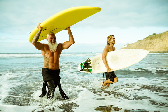 Best friends doing surfing in the summer time . People going out into the ocean. Sporty people lifestyle and extreme sport concept - Image