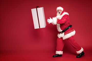 Happy Santa Claus on red studio background.