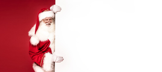 Real Santa Claus holding white empty board.