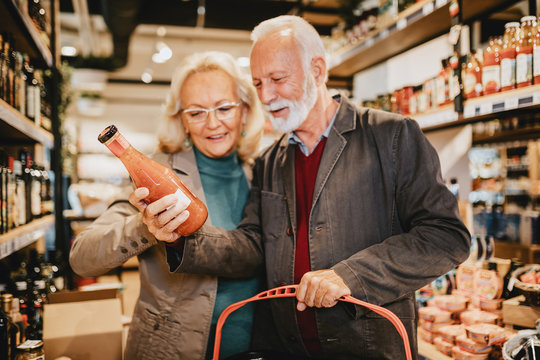 Happy senior couple shopping in grocery store or supermarket. Consumerism concept.