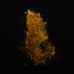 Orange spices powder explosion, flying pepper on black background. Freeze motion photo