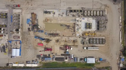 Fototapete - Oil and gas a land rig, onshore drilling rig, in the middle of a rice field aerial view from a drone