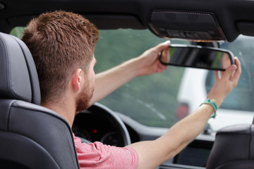 young man fitting rear view mirror in car