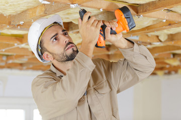 builder using cordless drill on wooden ceiling