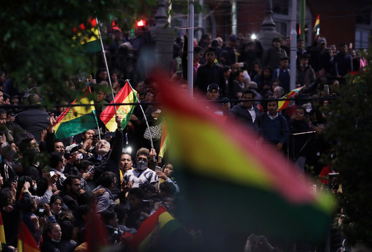 Supporters of Bolivian presidential candidate Carlos Mesa hold Bolivian flags as they protest next to national electoral computing center in La Paz