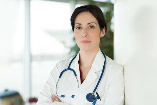 serious female doctor with crossed hands near window