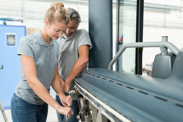 man and woman levering machinery