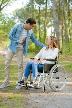 pretty woman in a wheelchair meeting man in the park