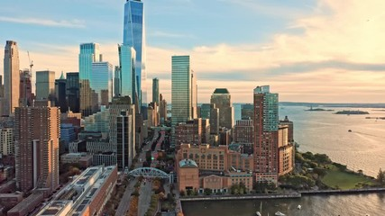 Fototapete - Drone footage with slow camera pull back along West Street in New York City on a sunny afternoon, before sunset
