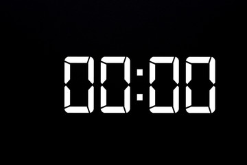 Showing time 00:00 on white led digital clock isolated black background