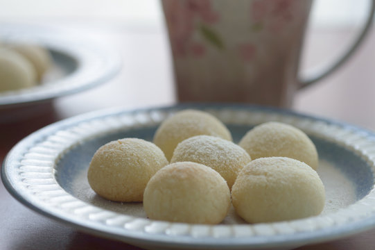 a plate of homemade snowball cookies on wooden table