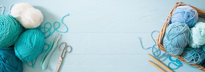 Yarn of green, turquoise, aquamarine and blue colors. White wood background. Knitting needles and crochet hooks. Scissors. Blue long background.