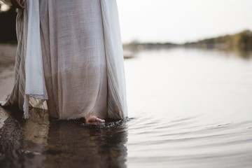 Closeup shot of a person wearing a biblical robe walking in the water near the shore