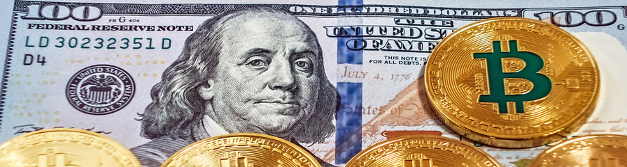 Gold bitcoin coin one hundred dollars bills.