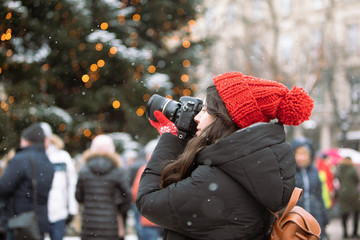 woman photographer with professional camera shooting outdoors at winter time