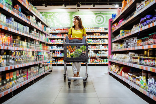 woman with shopping between store shelf portrait