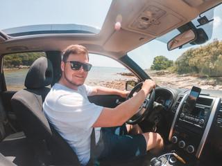 man sitting in car driving near summer sea beach