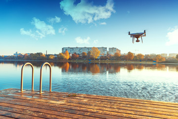 Wall Mural - Drone copter with digital camera, blur river on background
