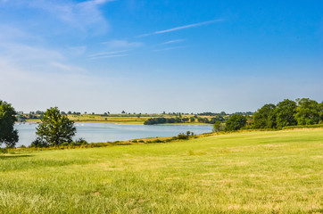 View across Rutland Water a large reservoir in Leicestershire with blue sky and grass.