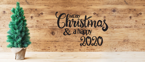 Brown Wooden Background WIth English Calligraphy Merry Christmas And A Happy 2020. Green Christmas...