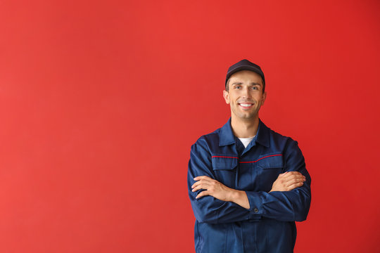 Male car mechanic on color background
