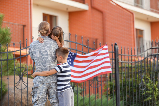 Sad little children saying goodbye to their military father outdoors