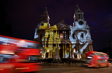 London buses pass as light projections depicting Second World War images are seen on the west face of St Paul's Cathedral as part of the forthcoming 'Where Light Falls' illuminations and poetry readings, in London
