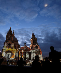 People view and record light projections depicting Second World War images seen on the west face of St Paul's Cathedral as part of the forthcoming 'Where Light Falls' illuminations and poetry readings, London, Britain