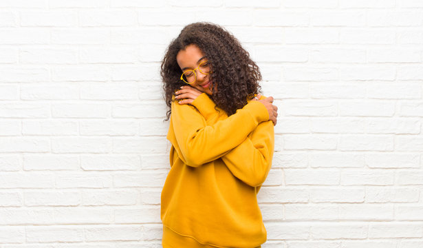 young black woman feeling in love, smiling, cuddling and hugging self, staying single, being selfish and egocentric against brick wall