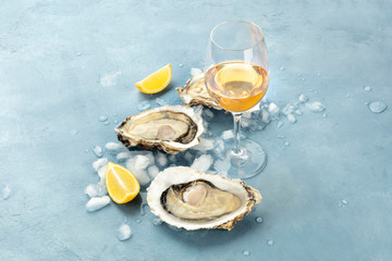 Fresh raw oysters on ice with a glass of white wine and lemon slices, with copy space