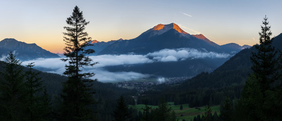 Seebensee reflection with Vorderer Drachenkopf mountain and coburger hut at sunrise Wall mural