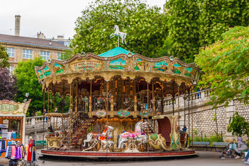 A lovely French old-fashioned style carousel with rows of wooden horses mounted on posts and a staircase to the second floor in the Louise Michel Square at the base of the butte Montmartre in Paris.