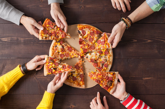 Taking slice of pizza. Friends eat pizza