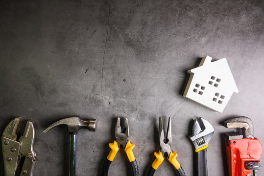 Wooden house and construction tools on stone pattern background with copy space.Home Repair concept, Repair maintenance concept, Renovation concept.