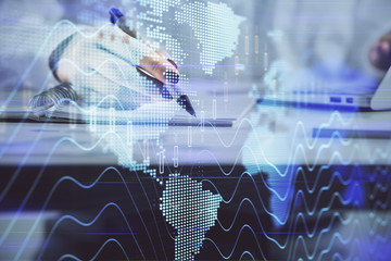 Double exposure of woman's hands making notes with forex graph hologram. Concept technical analysis.