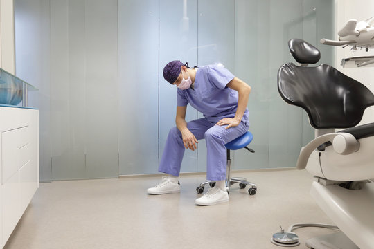 Tired dentist in his office sitting on stool, having break,waiting for patient in his office