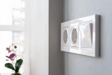 A closeup view of a group of white european electrical outlets and a switch located on a gray wall in a light modern kitchen by the window. Selective focus. Blurred background