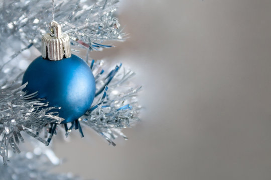 Closeup view of a blue matte ball hanging on a silver artificial Christmas tree with copy space for your text message. Selective focus. Blurred background. New Year's Eve home decoration