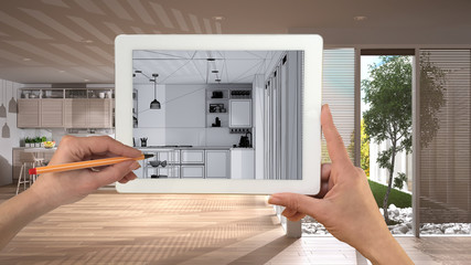 Hands holding and drawing on tablet showing modern white kitchen with wooden details CAD sketch. Real finished interior in the background, architecture design presentation