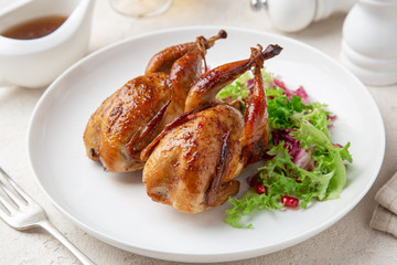 Whole roasted quail on white plate