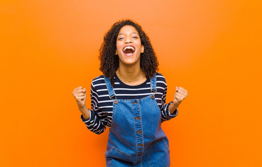young pretty black woman feeling shocked, excited and happy, laughing and celebrating success, saying wow! against orange wall