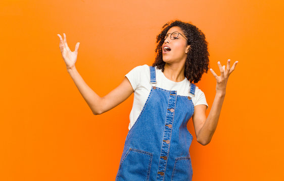 young pretty black woman performing opera or singing at a concert or show, feeling romantic, artistic and passionate against orange wall