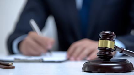 Gavel on block as jurisdictional symbol, attorney signing evidence on background