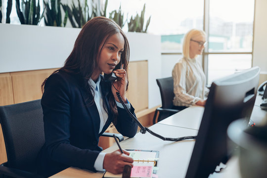 African American businesswoman taking a telephone message in an