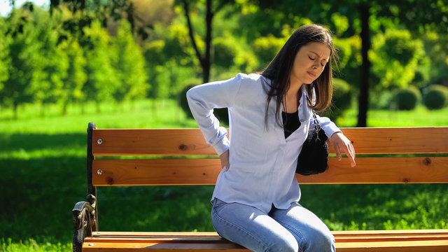 Woman with sharp back pain sitting on bench in park to rest, sedentary lifestyle