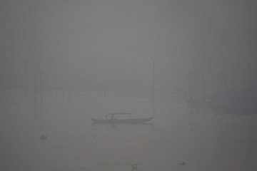 A boat passes as smoke covers Musi river due to the forest fire in Palembang